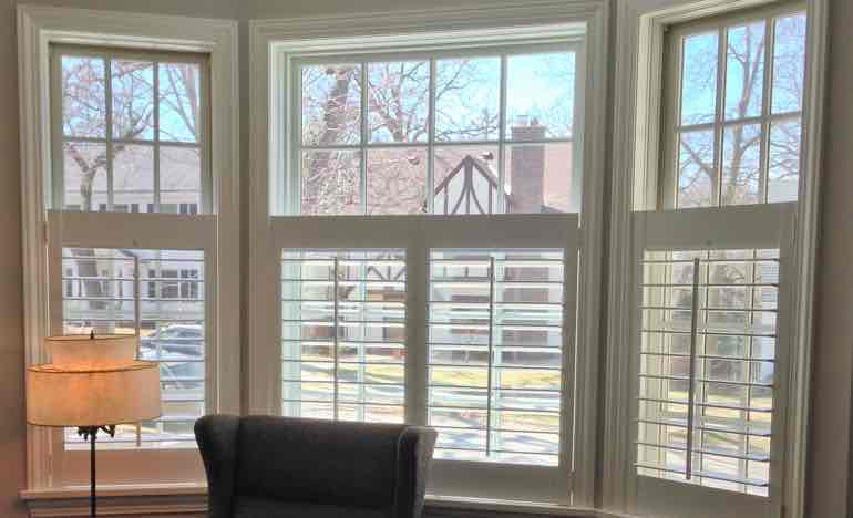 Half white shutters in family room bay window.