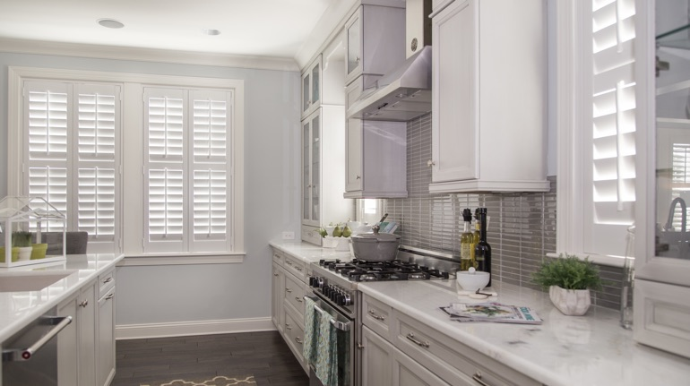 Plantation shutters in Southern California kitchen with white cabinets.