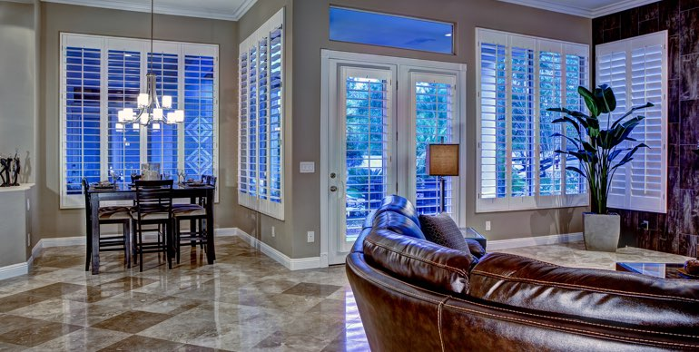 Southern California great room with white shutters and leather furniture.