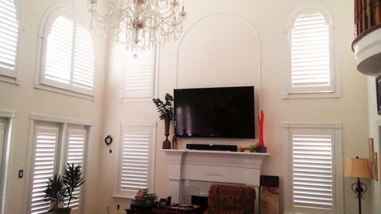 Southern California great room with wall-mounted television and arched windows.