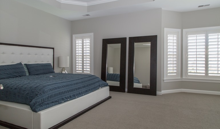 Polywood shutters in a minimalist bedroom in Southern California.