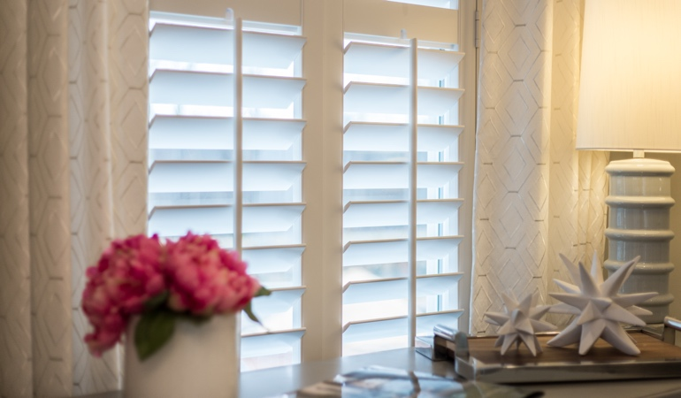 Plantation shutters by flowers in Southern California