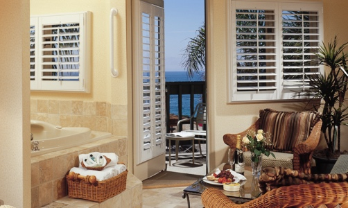 Plantation shutters on casement windows in a lakefront house.