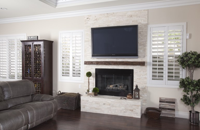 White plantation shutters in a Southern California living room with plank hardwood floors.