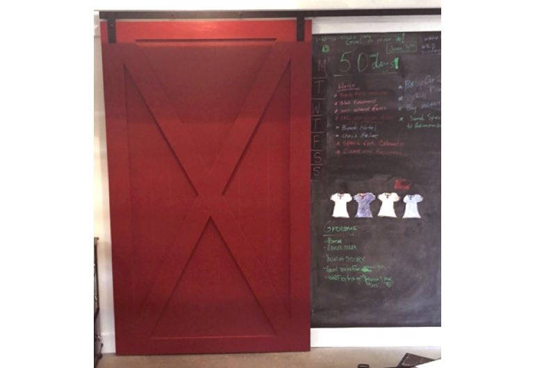 Bright red sliding barn door with black hardware next to chalkboard 🚪