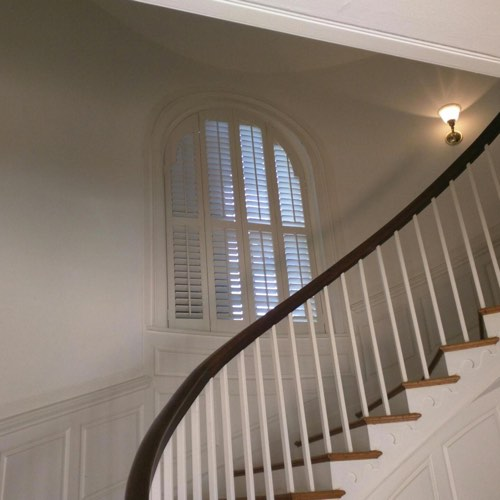 White plantation shutters decorating rounded window located in spiral stairwell.