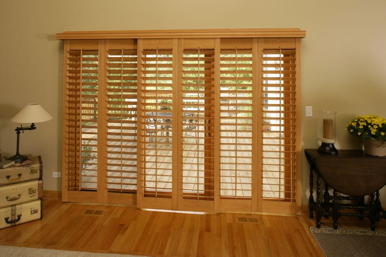 plantation shutters on sliding door connecting to full porch.