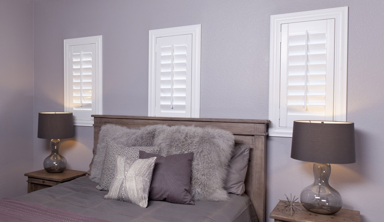White plantation shutters in Southern California bedroom windows.