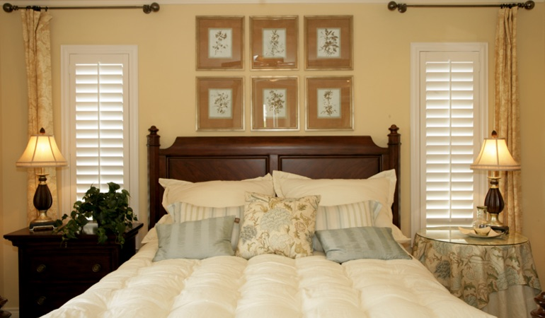Bedroom with two tall plantation shutters on either side of bed in Southern California