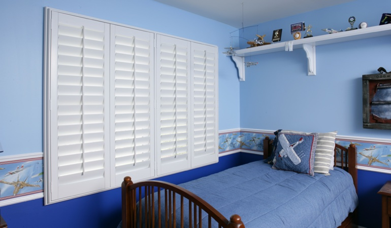 Large plantation shutters covering window in blue kids bedroom in Southern California