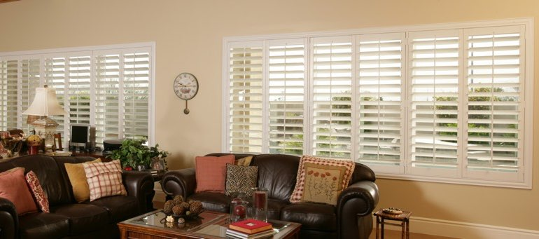 Wide window with white shutters in Southern California living room